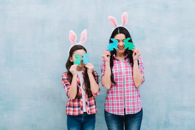 Mère, fille, tenue, papier, découpe, lapin, devant, yeux, contre, mur bleu Photo gratuit