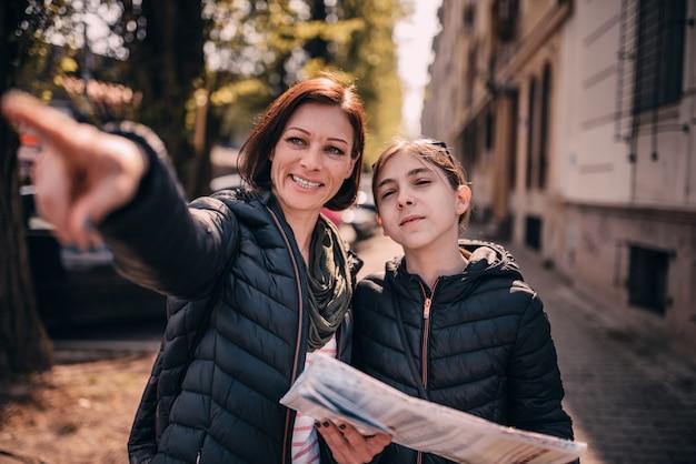 Mère et fille touristique à l'aide de la carte de la ville Photo Premium