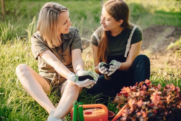 Mère avec une fille travaille dans un jardin près de la maison Photo gratuit