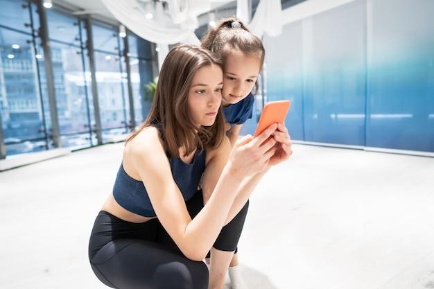 Mère Fille, Utilisation, Téléphone, Dans, Gymnase, Pour, Regarder Vidéo Photo gratuit