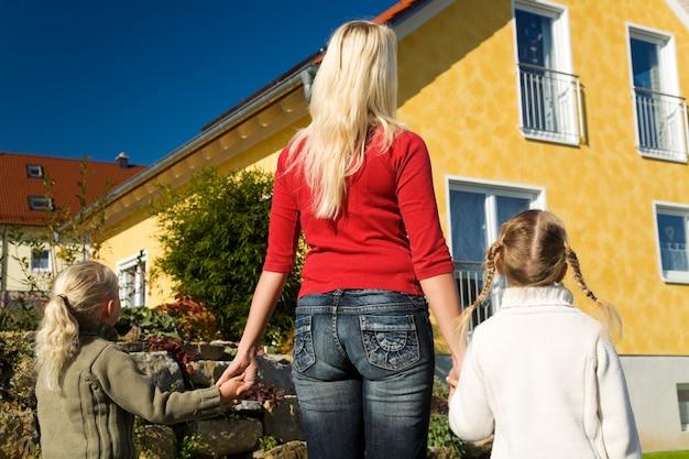 Mère et filles regardant leur maison Photo Premium