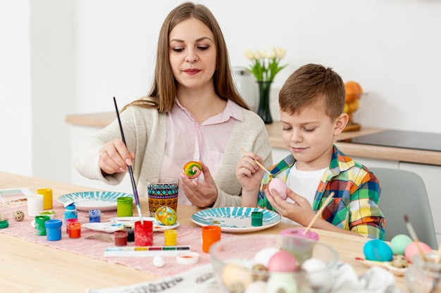 Mère Et Fils à Angle élevé Concentrés Pour Peindre Des œufs Photo gratuit
