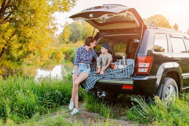La mère et le fils de l'enfant se relaxent confortablement dans la nature au bord de la rivière, assis sur le coffre d'une jeep. Photo Premium