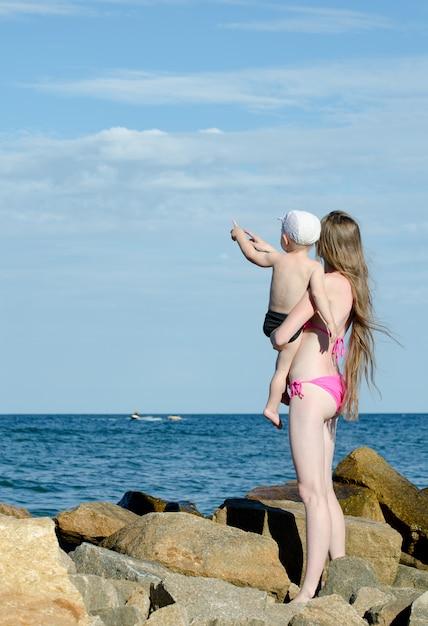 Mère et fils sur les mains sont parmi les pierres sur le bord de la mer, montrent au loin Photo Premium