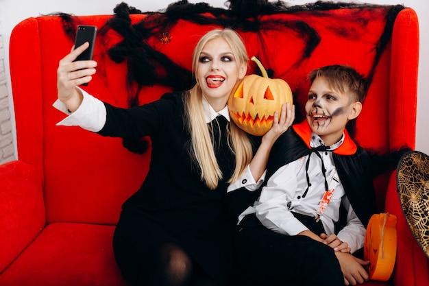 Mère et fils passent un moment amusant sur un canapé rouge et font un gros plan de selfie. emotion et halloween Photo Premium