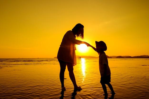 Une mère et un fils en plein air au coucher du soleil avec un espace de copie Photo gratuit