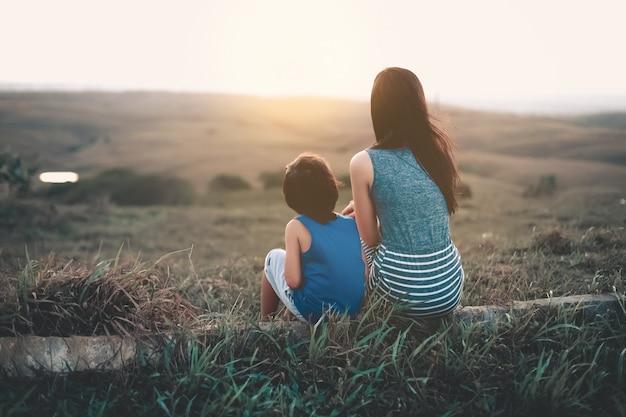 Mère et fils en regardant le coucher de soleil à l'horizon Photo Premium
