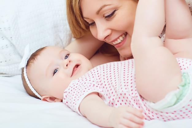 Une mère heureuse avec un bébé joue sur un lit dans une pièce à l'intérieur. fête des mères. Photo Premium