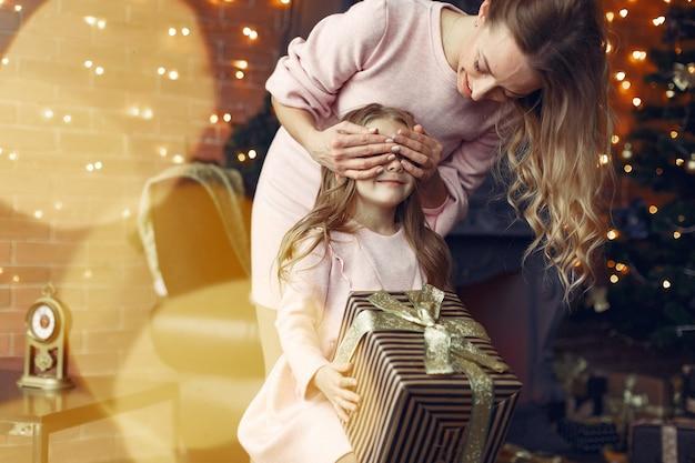 Mère Avec Jolie Fille à La Maison Près De Cheminée Photo gratuit