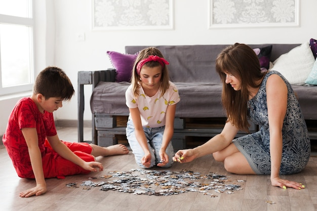 Mère jouant au puzzle avec ses enfants à la maison Photo gratuit