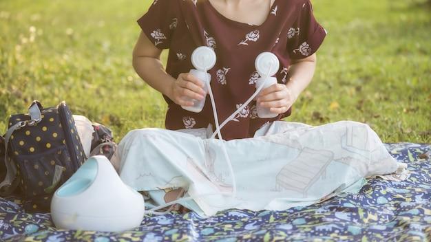 Mère, lait maternel dans un parc au coucher du soleil Photo Premium