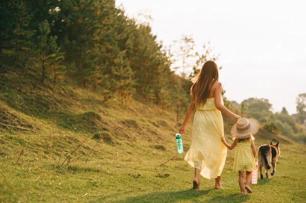 Mère marcher avec sa petite fille et leur chien Photo Premium