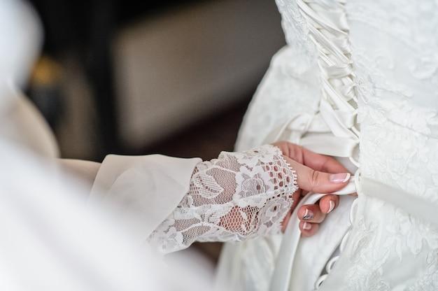 La mère de la mariée aide à attacher la robe de mariée Photo Premium