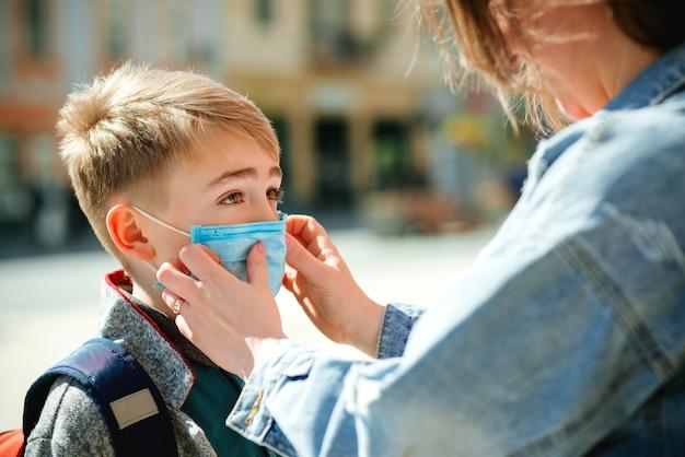 La Mère Met Un Masque De Sécurité Sur Le Visage De Son Fils. L'écolier Est Prêt à Aller à L'école. Retour Au Concept De L'école. Photo Premium