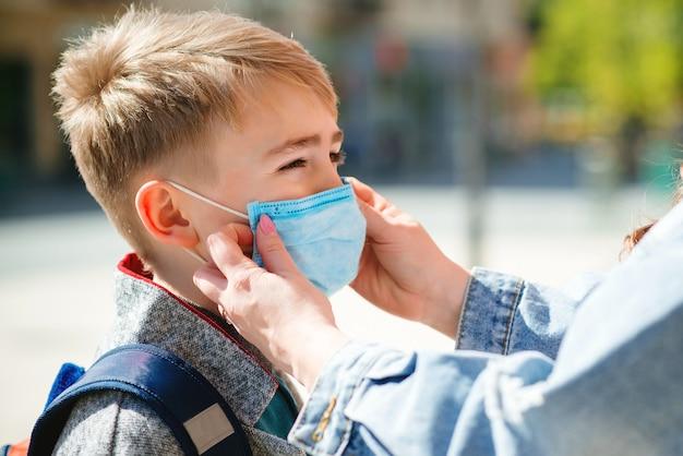 La Mère Met Un Masque De Sécurité Sur Le Visage De Son Fils. Masque Médical Pour Prévenir Les Coronavirus. Quarantaine Face Au Coronavirus Photo Premium
