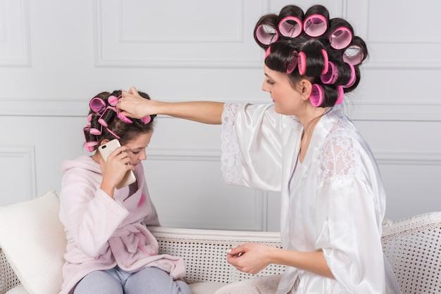 Mère Mettant Le Bigoudi Rose Dans Les Cheveux Des Filles Photo gratuit