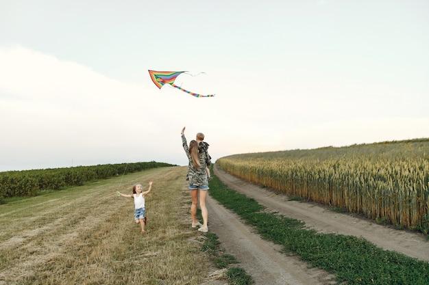 Mère avec mignons petits enfants dans un champ d'été Photo gratuit