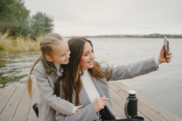 Mère à La Mode Avec Sa Fille. Les Gens En Pique-nique. Femme En Manteau Gris. Famille Au Bord De L'eau. Photo gratuit