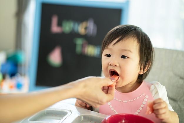 Mère Nourrir La Pastèque à Un Jeune Enfant Mignon Sur Une Chaise Haute Pour Bébé à La Maison, Profiter D'un Repas Et Ouvrir La Bouche Pour Manger Des Fruits Sucrés. Photo Premium