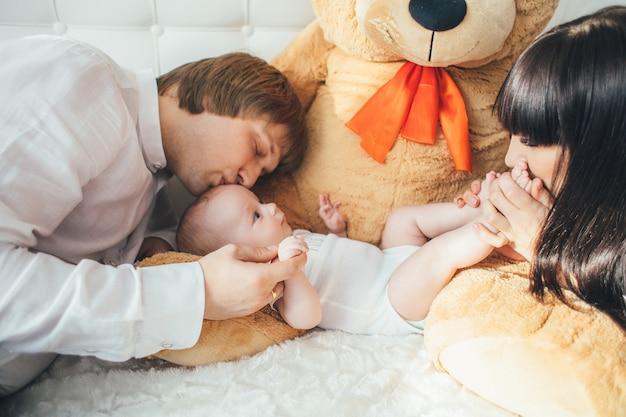 La mère, le père et le fils se trouvent près de l'ours sur le lit Photo gratuit