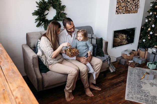Mère, père et leur jolie fille échangeant des cadeaux de noël Photo Premium