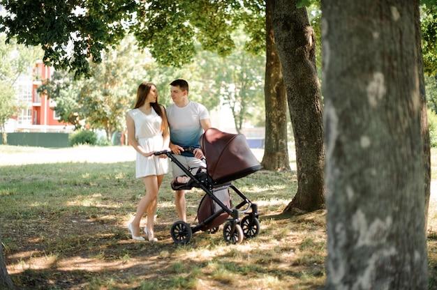 Mère, Père Et Leur Petite Fille Dans Le Chariot De Babby Photo Premium
