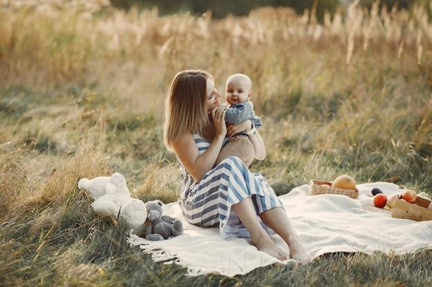 Mère avec petit fils assis dans un champ d'automne Photo gratuit