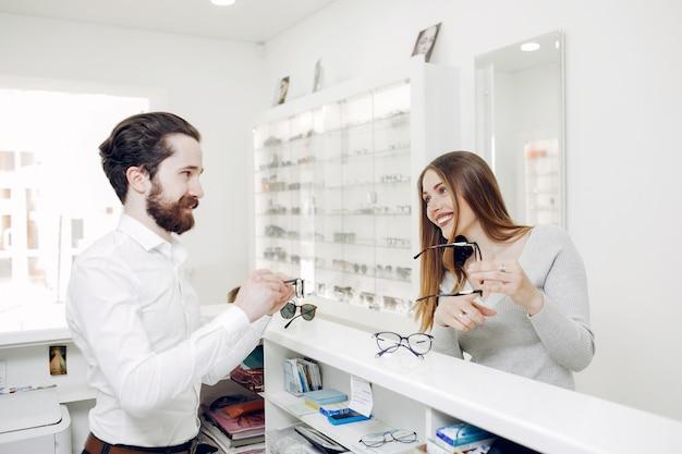 Mère avec petit fils dans le magasin de lunettes Photo gratuit