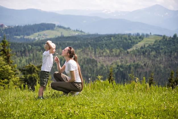 Mère et petit fils soufflent des montagnes et des forêts de pissenlit. maternité et amitié Photo Premium