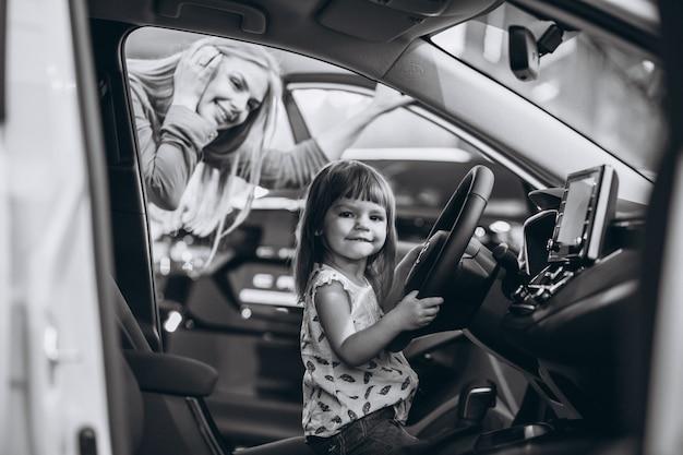 Mère avec petite fille assise dans une voiture dans une salle d'exposition Photo gratuit