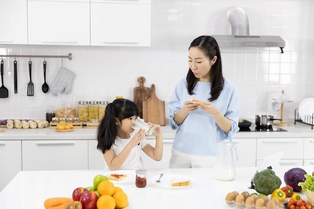 Mère et petite fille déjeunent dans la cuisine de la maison Photo Premium