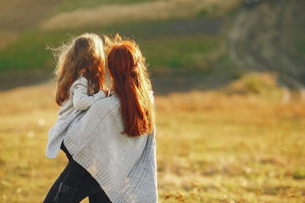 Mère avec petite fille jouant dans un champ d'automne Photo gratuit