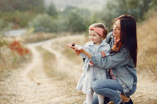 Mère avec petite fille jouant dans un champ avec un papillon Photo gratuit