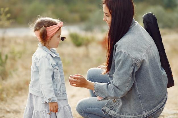 Mère avec petite fille jouant dans un champ Photo gratuit