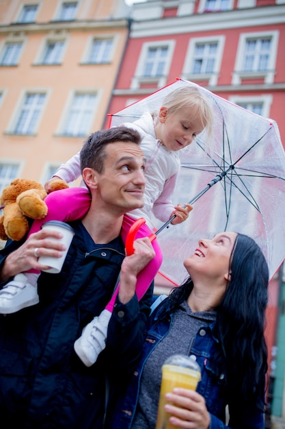 Mère, petite fille avec parapluie et père en ville Photo Premium