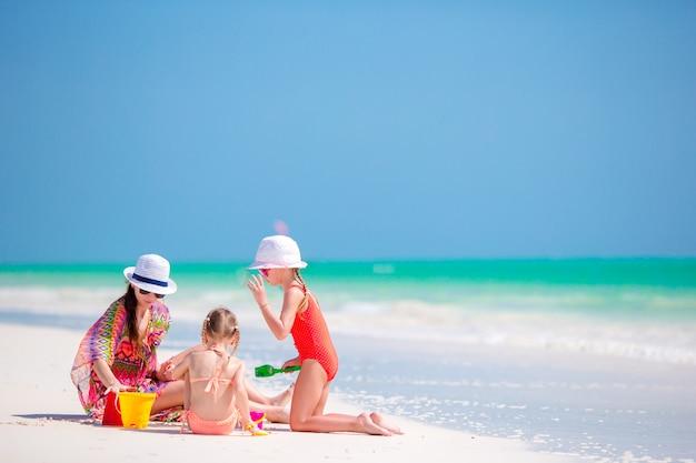 Mère et petites filles faisant un château de sable sur une plage tropicale Photo Premium