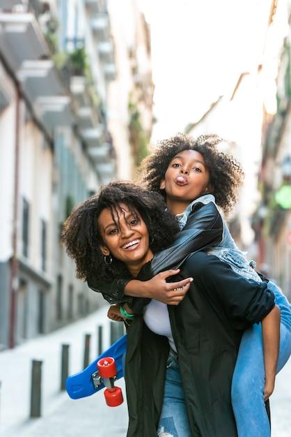 Mère portant sa fille sur le dos Photo Premium
