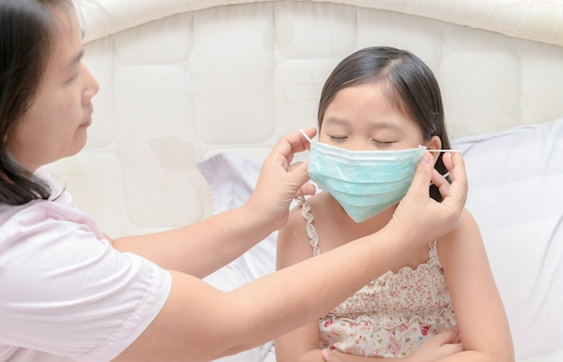 Mère porter une fille masque de protection pour se protéger contre le virus de la grippe dans la chambre à coucher, les soins de santé et Photo Premium