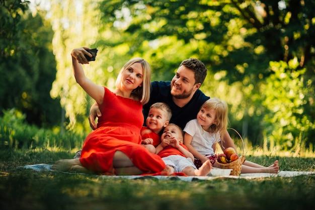 Mère prenant une famille selfie à l'extérieur Photo gratuit