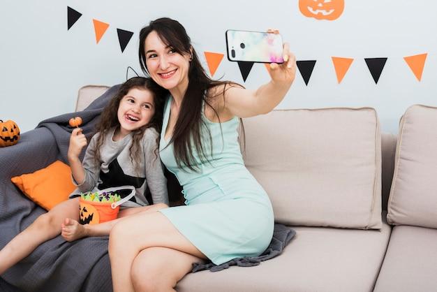 Mère prenant un selfie avec sa fille à l'halloween Photo gratuit