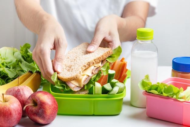 Mère préparant le coffret repas scolaire Photo Premium