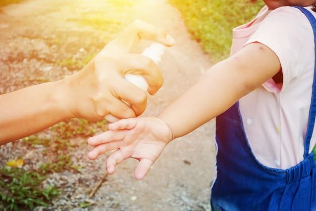 Mère Pulvérisant Des Insectifuges Ou Des Répulsifs Contre Les Moustiques Sur La Peau De La Fille, Anti-moustique Pour Les Bébés Photo Premium