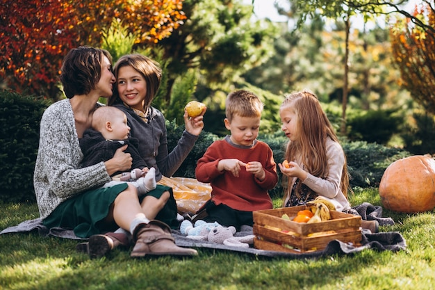 Mère avec quatre enfants ayant pique-nique dans la cour arrière Photo gratuit
