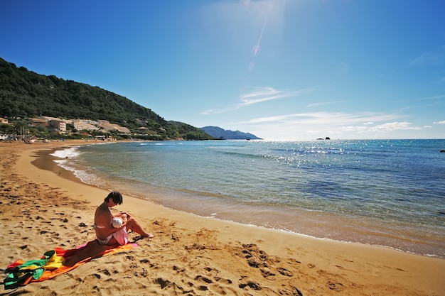 Mère qui allaite un enfant sur la plage Photo Premium