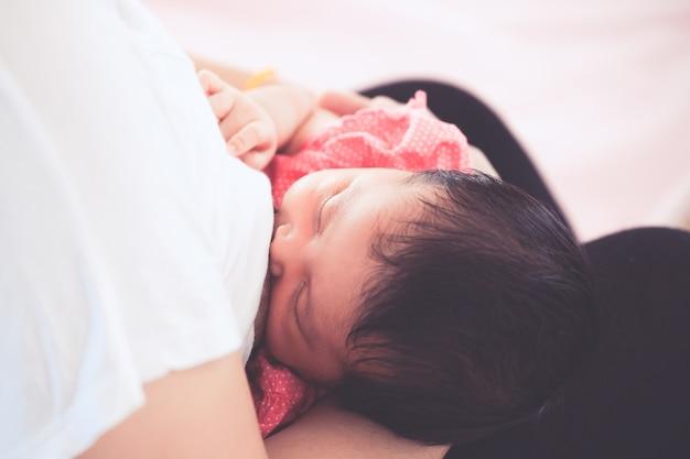 Mère qui allaite sa petite fille nouveau-née. Photo Premium