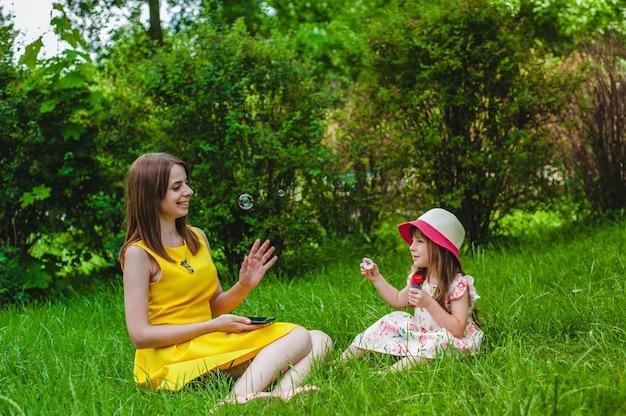 Mère Regardant Sa Fille Souffle Des Bulles De Savon Photo gratuit
