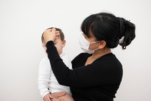 Mère s'inquiète pour son fils, tombe malade, touche son front pour vérifier. Photo Premium
