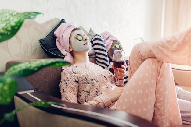 La Mère Et Sa Fille Adulte Ont Appliqué Des Masques Pour Le Visage Et Des Concombres Sur Les Yeux. Femmes Se Refroidissant En Buvant Du Vin Photo Premium