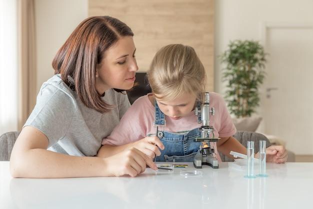 Une mère et sa fille font des expériences chimiques avec un microscope à la maison Photo Premium