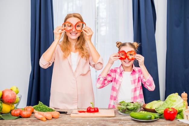 Mère et sa fille tenant un poivron rouge devant leur maison Photo gratuit